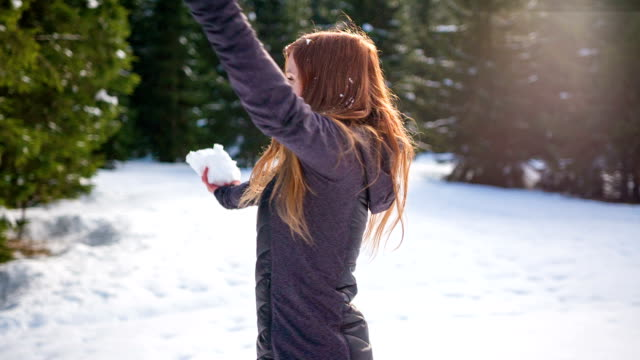 Young woman dancing in the snow