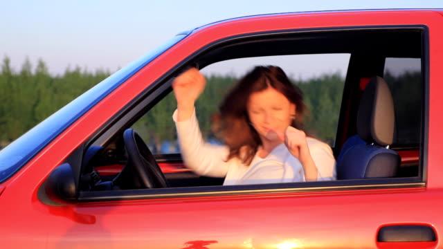 Giovane donna ballando in auto e la guida.