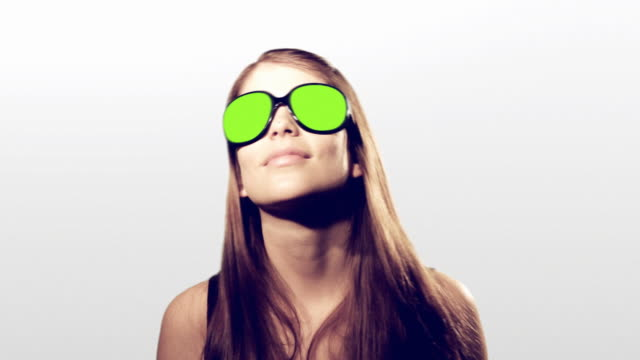Young woman dancing with blinking colors sunglasses