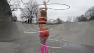 A young woman dancing with hula hoops in a bright costume.