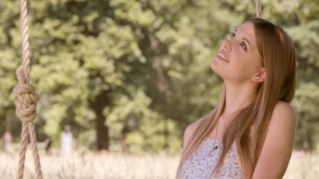SLO MO giovane donna sognare ad occhi aperti su un Altalena in Natura