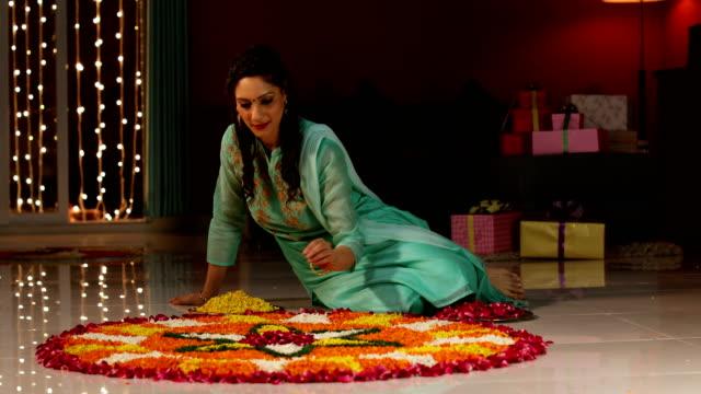 Young woman decorating rangoli, Delhi, India