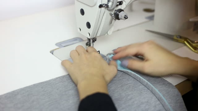 Young woman designer working at sewing machine.