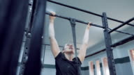 Young woman determined to do chin-ups on fixed bar.