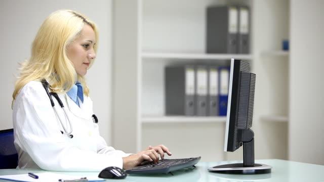 Junge Frau Doktor Tippen auf desktop-computer in Arzt-Büro