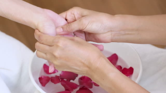Young woman doing hand spa massage