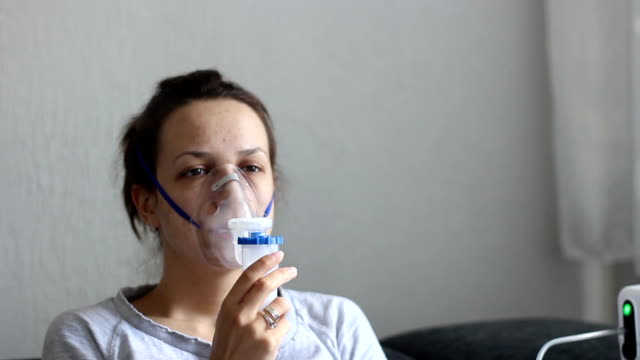 young woman doing inhalation at home