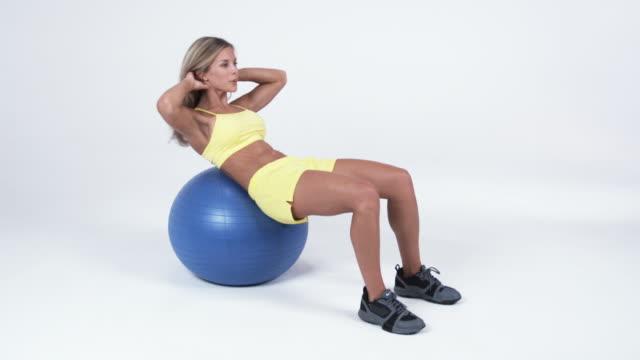 WS Young woman doing sit ups on exercise ball / Orem, Utah, USA