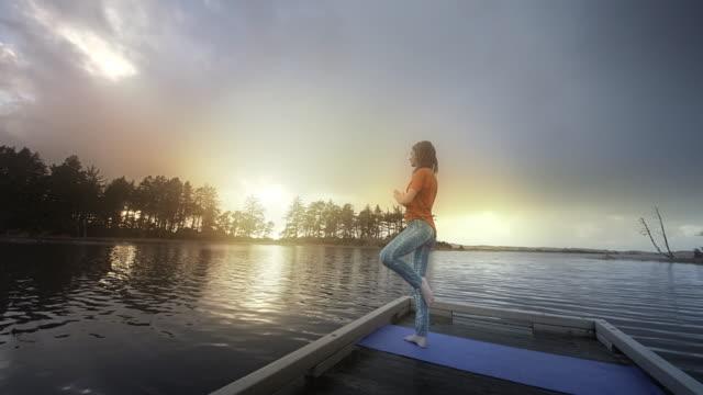 Young woman doing Yoga on dock of a lake at sunset, Oregon