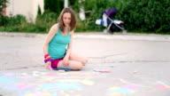 young woman draws a chalk on asphalt, close up