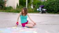 young woman draws a chalk on asphalt on playground