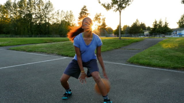 MS Young woman dribbling basketball on outdoor court on summer evening