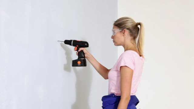 Young woman drilling a hole in wall