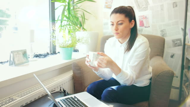 Young woman drinking a cup of tea while using laptop.