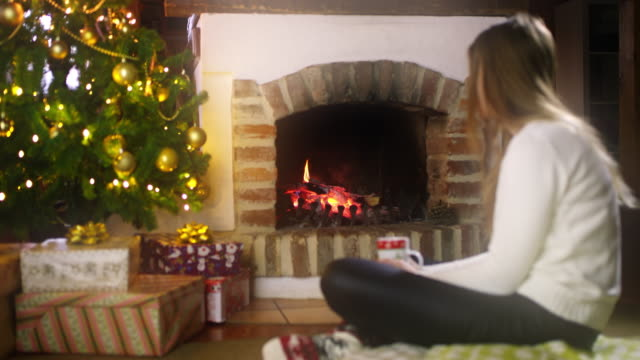 DS Young woman drinking a tea by the fireplace