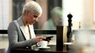 Junge Frau Kaffee trinken und mit tablet