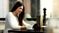 Young woman drinking coffee and using tablet