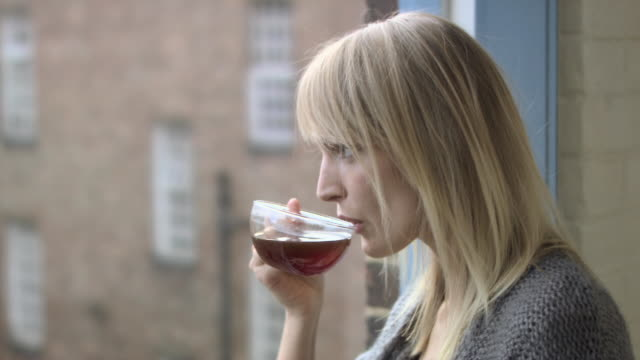 Young woman drinking herbal tea and speaking to someone who is out of shot