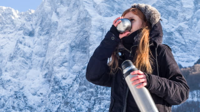 Young woman drinking out of a thermos in winter landscape