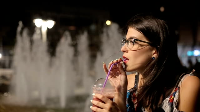 Young woman drinking strawberry smoothie on the street,night scene