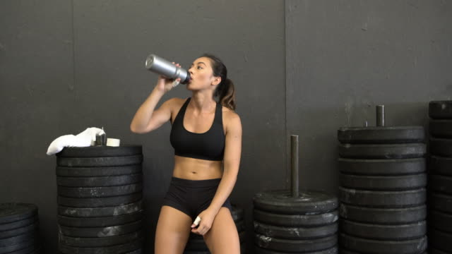 MS Young woman drinking water while working out in a gym