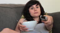 MS Young woman eating cereal and watching television / London, United Kingdom