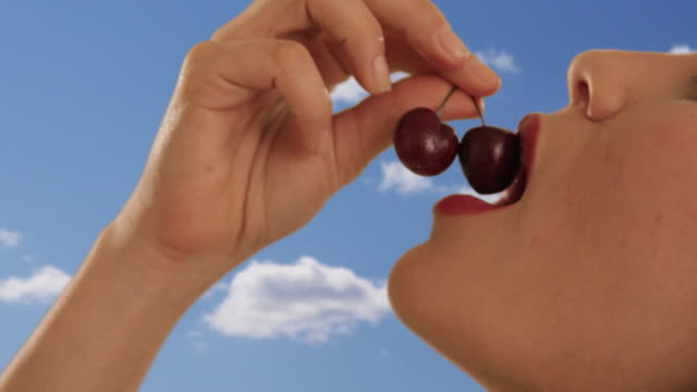 young woman eating cherries