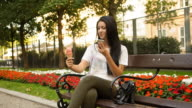 Young woman eating ice cream and photo messaging with phone
