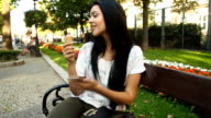 Young woman eating ice cream and playing with phone