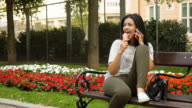 Young woman eating ice cream and talking on the phone