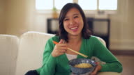 MS Young woman eating noodles at home looking off camera.