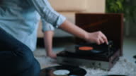 Young woman enjoing music from gramophone