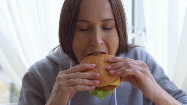 Junge Frau, die einen großen Hamburger zu Hause genießen