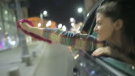Young woman enjoying a car ride in the night.