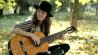 Young woman enjoying playing guitar in the park on summer