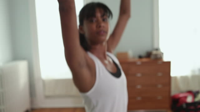 CU TU R/F Young woman exercising in bedroom / Brooklyn, New York City, USA