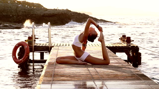 Young woman exercising yoga on the quay slow motion