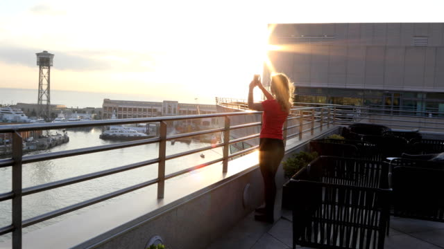 Young woman explores seafront harbour area of city at sunrise, Barcelona