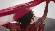 MED SLO MO. Young woman facing mountains holds up flowing red scarf in the wind.