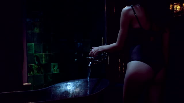 MS TU Young woman filling bathtub with water