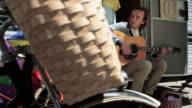 Young woman filming boyfriend as he plays guitar outside caravan