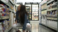 Young woman finding a broken jar in a warehouse supermarket