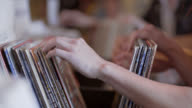 Young woman flips through vinyl records looking for bargains in Austin music shop