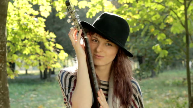 Young woman flirting, posing in park, holding guitar, smiling outdoors.