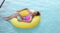 WS Young woman floating in inflatable ring in swimming pool / Richmond, Virginia, USA