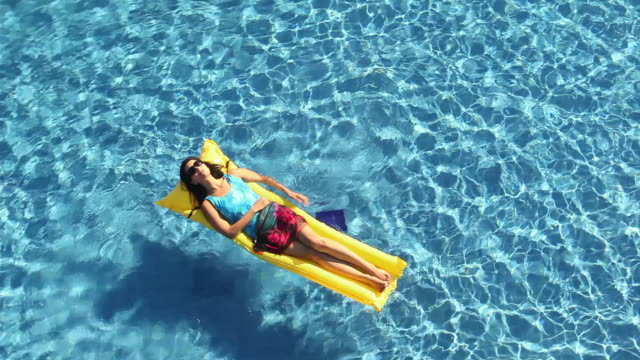Young woman floating on a inflatable bed in a swimming pool