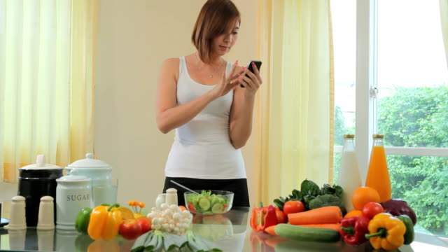 Young woman Following Recipe On mobile phone