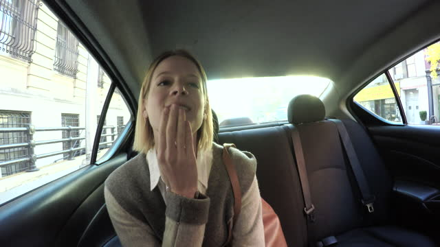 Young woman gets into back seat of car, daytime