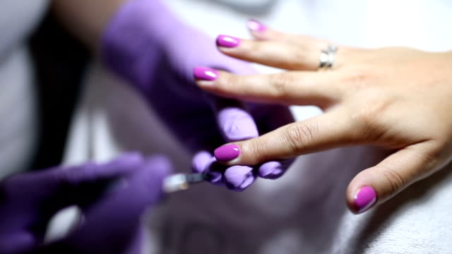 Young woman getting her pink polish in beauty salon