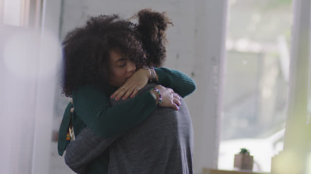 MS SLO MO. Young woman gives long comforting hug to boyfriend in coffee shop.